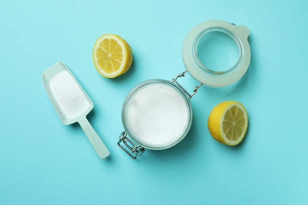 Scoop and jar with acid powder and halves of lemon on blue isolated background