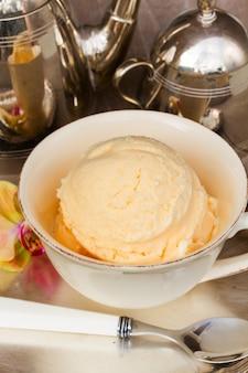 Шарик ванильного мороженого подается в чашке крупным планом