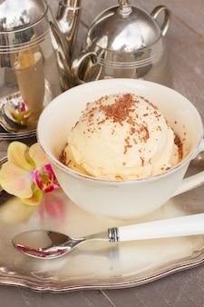 Шарик ванильного мороженого с шоколадом подается в чашке