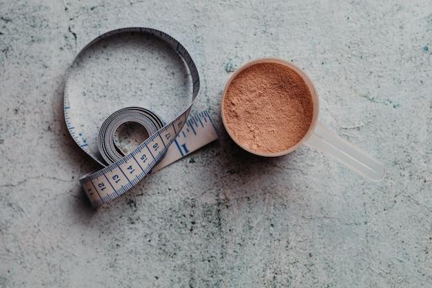 目に見える質感のホエイプロテインのスクープまたはスプーン。チョコレート味。コンクリートの背景
