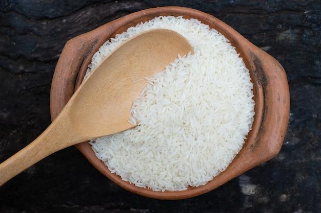 나무 배경에 있는 항아리에 국자를 사용하여 쌀을 퍼내다
