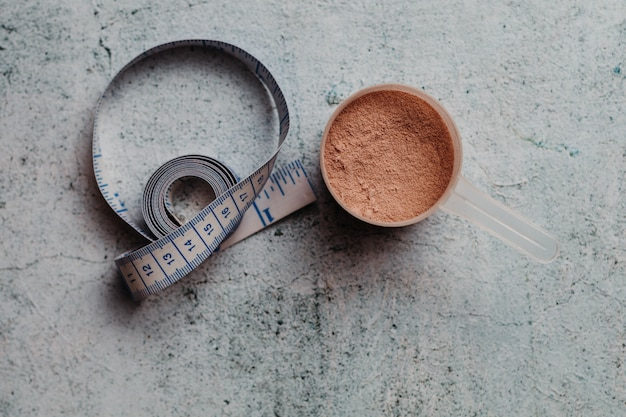 Scoop or spoon of whey protein with visible texture. chocolate flavor. concrete background