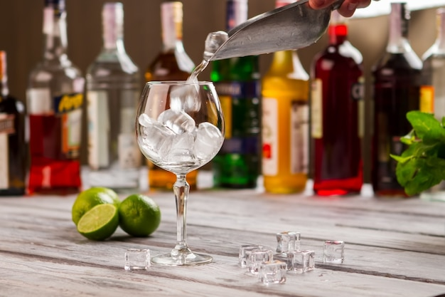 ワイングラスの上に氷ですくう。角氷の近くのライム。冷たい飲み物を準備しています。さっぱりする必要があります。