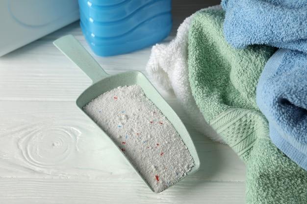 Совок с порошком, моющим средством и полотенцами на белом деревянном фоне