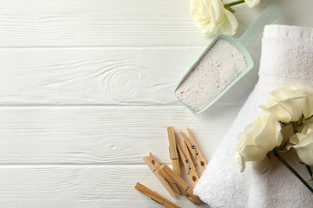 Совок с порошком, розами и полотенцами на белом деревянном