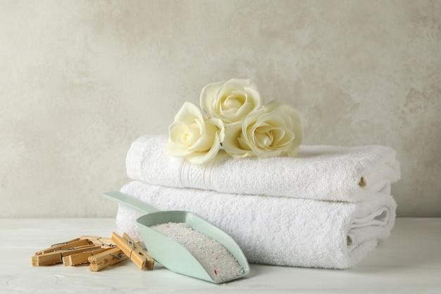 Совок с порошком, розами, прищепками и полотенцами на белом деревянном столе