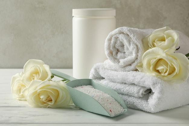 Совок с порошком, розами, пластиковой банкой и полотенцами на белом деревянном столе