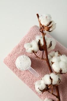Совок со стиральным порошком, хлопком и полотенцем на белом фоне
