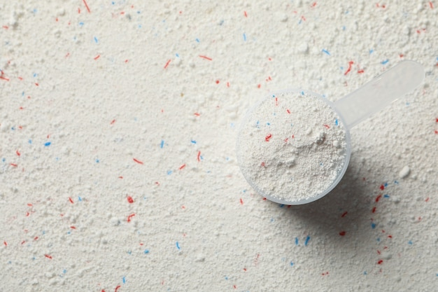 Scoop with washing powder on washing powder table