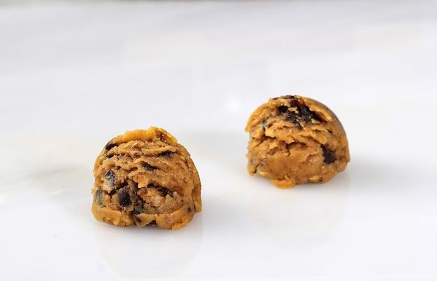 白の背景に分離された、すくい取った生チョコレートチップクッキーの混合物