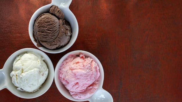 小さな白いセラミックカップに入ったさまざまなフレーバーのアイスクリームのスクープ