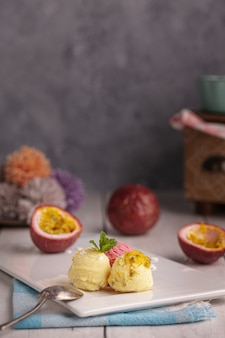 木製のテーブルの上の白いプレートに情熱、バニラとイチゴのアイスクリームのスクープ