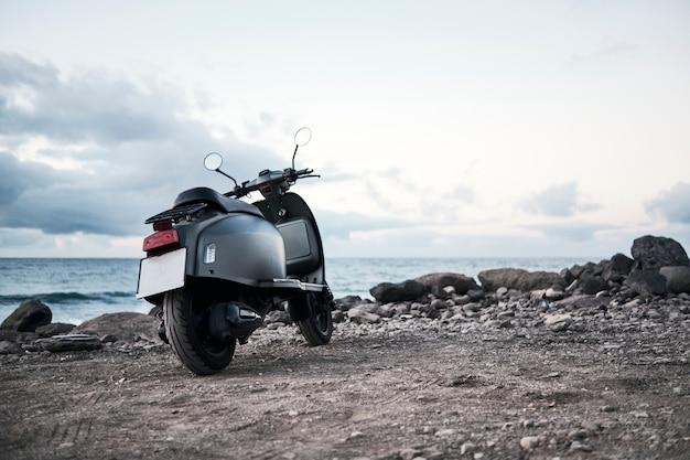 ビーチの岩の多い海岸にスクーターモーターバイク