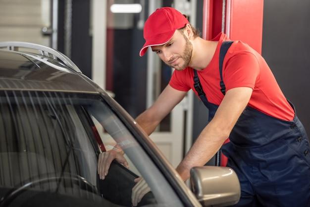作業範囲。ワークショップで開いている車の窓を覗く作業服に興味のある若いひげを生やした男