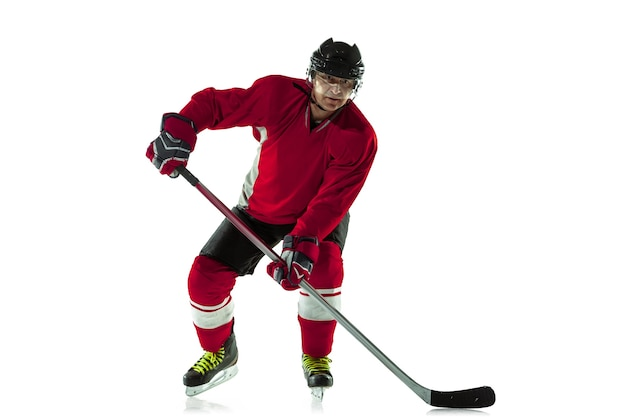 Scoring a goal. male hockey player with the stick on ice court and white wall. sportsman wearing equipment and helmet practicing. concept of sport, healthy lifestyle, motion, movement, action.