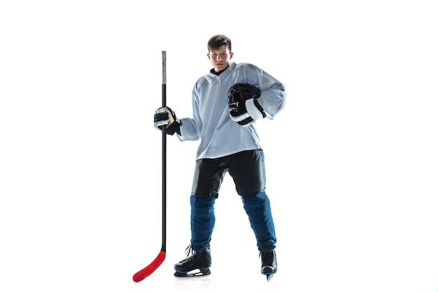 득점. 아이스 코트와 흰색 배경에 막대기로 젊은 남자 하키 선수. 장비와 헬멧 연습을 착용하는 스포츠맨. 스포츠, 건강한 라이프 스타일, 운동, 운동, 행동의 개념.