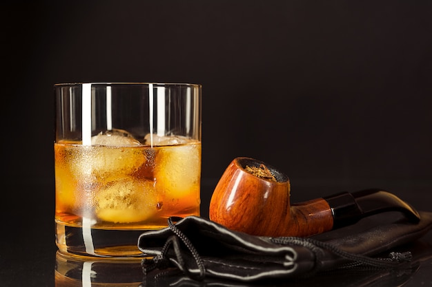 Scotch drink glass and smoking pipe