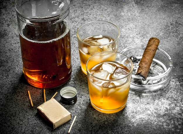 Scotch whiskey with a cigar. on a rustic background.