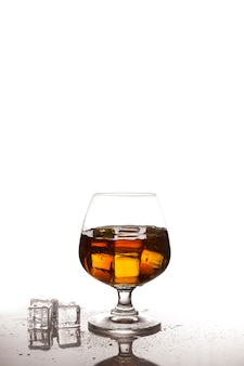 Scotch whiskey with ice in glass on table white background