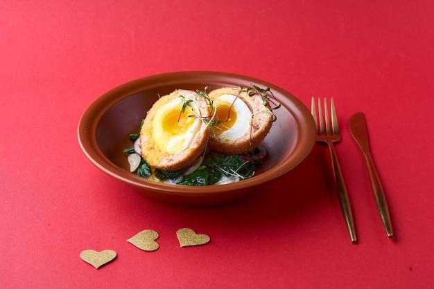 스코틀랜드 계란. 접시에 연어, 무, 시금치와 스코틀랜드 계란