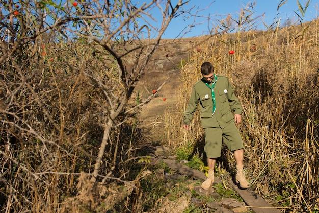 スカウトは、制服を着た荒野の小道を横断しながら、小川を渡る狭い丸太橋に注意深く浸っています。