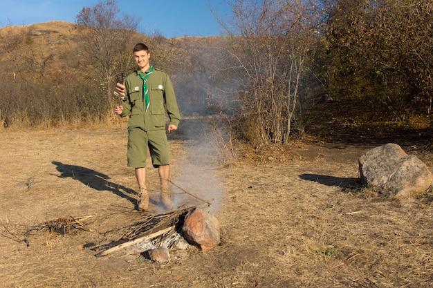Разведчик или рейнджер разводит костер на поляне в луговой растительности, чтобы приготовить себе обед, стоя, улыбаясь в камеру