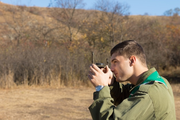 탐색에 사용하여 황야를 횡단할 때 눈으로 정렬된 나침반으로 관찰하는 스카우트 또는 레인저