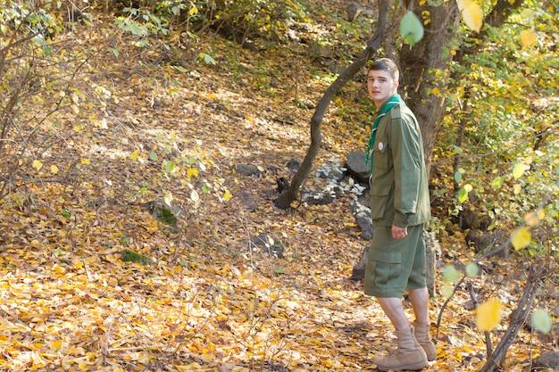スカウトまたはレンジャーが制服を着て森の中を歩き、コピースペースを持って通り過ぎるときにカメラを見ます