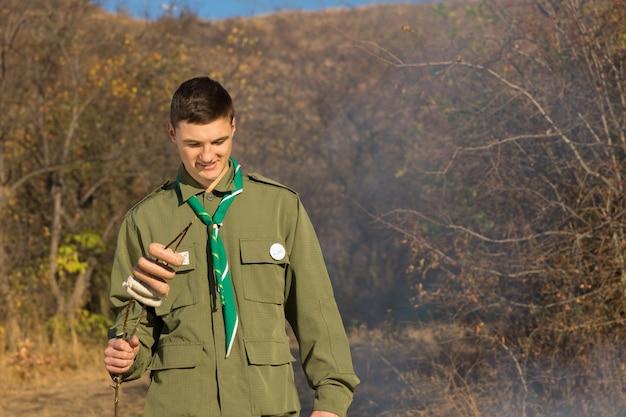 Разведчик готовится варить сосиски на костре, стоя, глядя на дым, держа колбаски на вертеле или палке.
