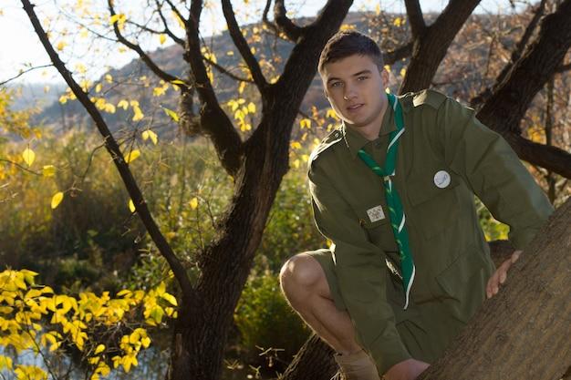 カラフルな黄色い秋の木に立っているスカウトは、カメラを直接見て自分の場所を確立しようとします