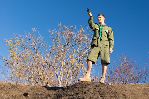 자신의 방위와 위치, 낮은 각도의 스카이라인 보기를 얻기 위해 나침반을 읽는 바위 위에 서 있는 스카우트
