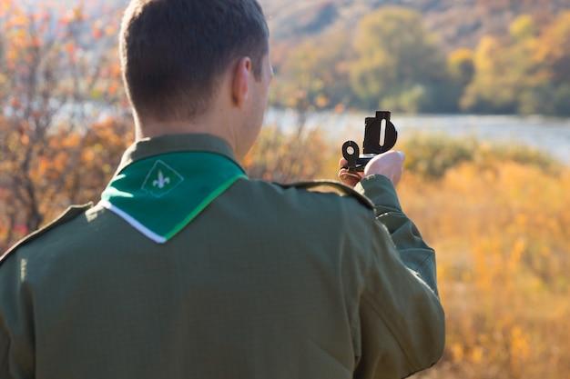 자신의 지리적 위치를 찾기 위해 자북을 사용하여 시골 강을 향한 나침반으로 관찰하는 정찰병