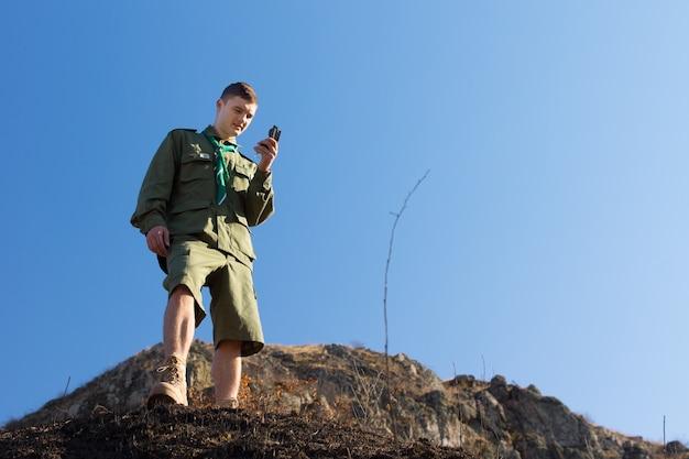 자기 나침반을 사용하여 탐색하는 스카우트는 푸른 하늘을 배경으로 자기 북쪽을 읽는 절벽에 서 있는 산의 황야를 탐험합니다.
