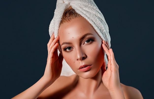 彼女の頭にタオルで彼女のにきびのショックでしかめっ面の女の子。女性のスキンケアの概念/灰色の背景に醜い問題の肌の女の子の写真
