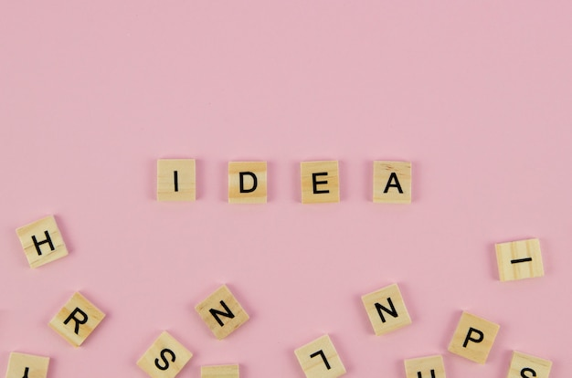 Scrabble letters and idea word concept on pink background