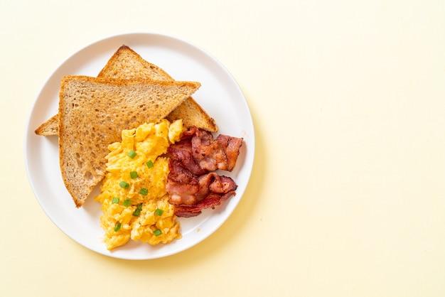 아침에 구운 빵과 베이컨을 곁들인 스크램블 에그