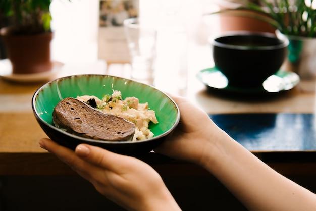 손에 계란과 빵의 스크램블 플레이트, 선택적 초점
