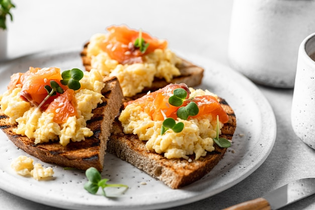 Scrambled egg sandwich with salmon on a ceramic plate on a white background selective focus closeup