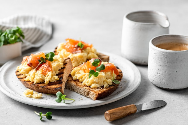Scrambled egg sandwich with salmon on a ceramic plate on a white table, selective focus