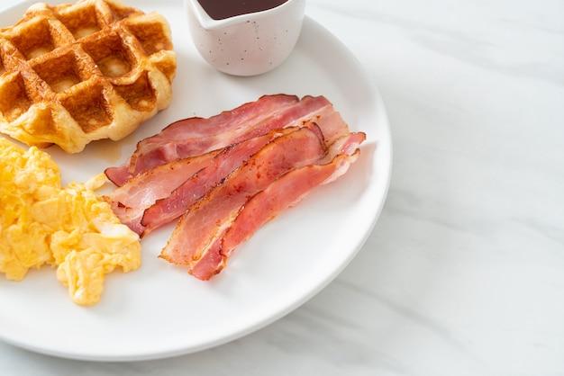 朝食にベーコンとワッフルを添えたスクランブルエッグ
