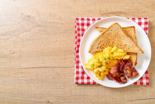 朝食にトーストしたパンとベーコンのスクランブルエッグ
