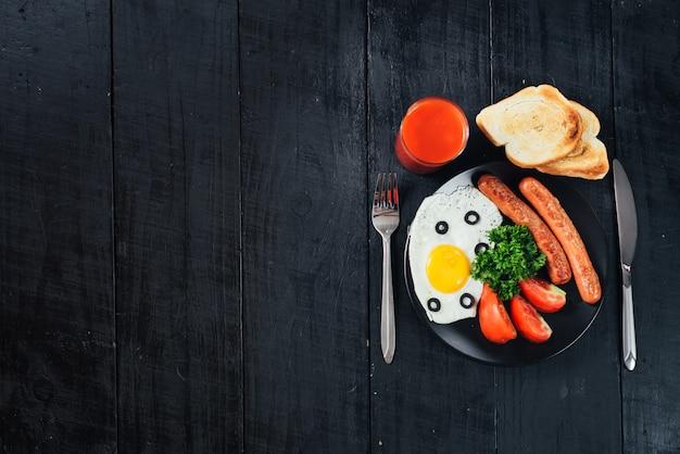 Яичница с сосисками в сковороде и томатный сок на черном фоне. копировать пространство