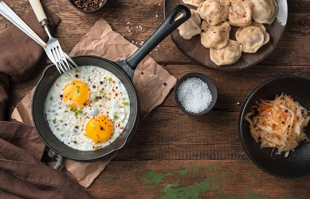 Яичница и пельмени на деревянном фоне. вид сверху. концепция приготовления пищи.