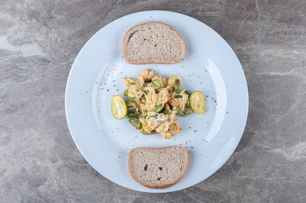 Scrambled eggs and bread slices on white plate.