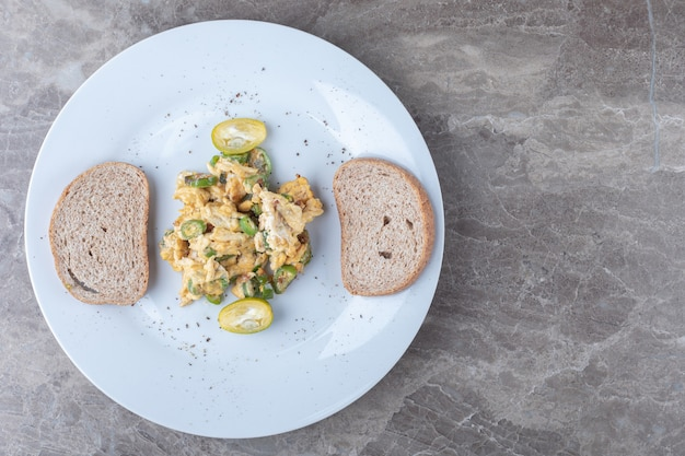 Scrambled eggs and bread slices on white plate. Free Photo