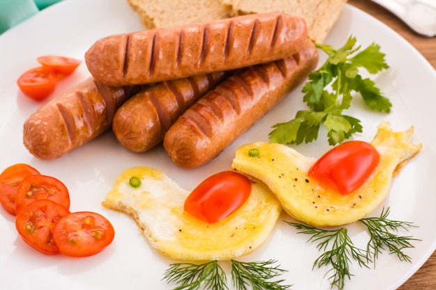 Scrambled eggs, cherry tomatoes and fried sausages