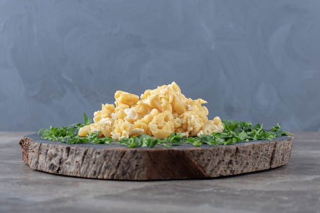 Scrambled eggs decorated with greens on wood piece.