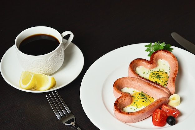 Scrambled eggs in the form of heart on a white plate with sausages