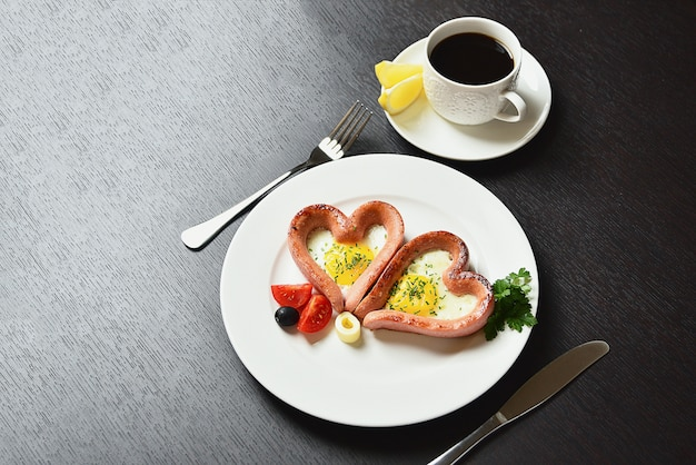 Scrambled eggs in the form of heart on white plate