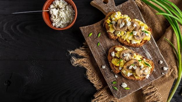 スクランブルエッグフレンチトーストと新鮮なキノコ、おいしい朝食または素朴なテーブルでの軽食。